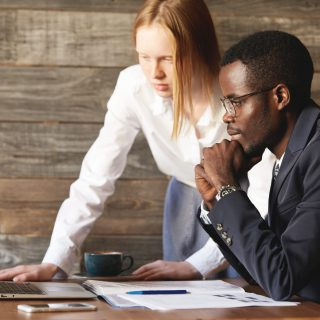 Business and career concept. Teamwork and cooperation: African man in formal suit and Caucasian woman in white shirt videoconferencing and negotiating with their partners using generic laptop