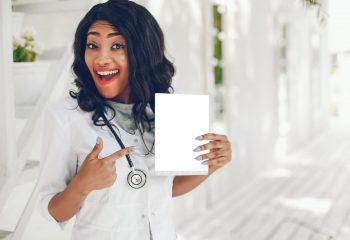 Stylish black doctor in a white uniform. Lady with stethoscope. Woman with book
