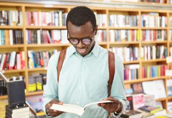 Handsome young Afro American hipster in shades holding open book in his hands, reading his favorite poem, searching for inspiration in public library or bookstore. People, lifestyle and leisure