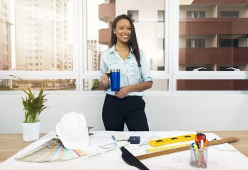 smiling-african-american-lady-with-vacuum-cup-near-plan-table-with-equipments